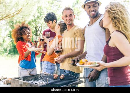 Multi-etnico gruppo di amici di parlare e si diverte a un barbecue party Foto Stock