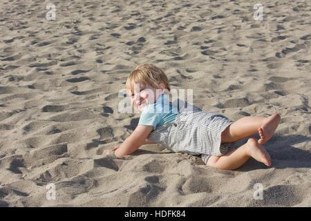 Giovane ragazzo toddler indossando tute e giocando sulla spiaggia di sabbia Foto Stock