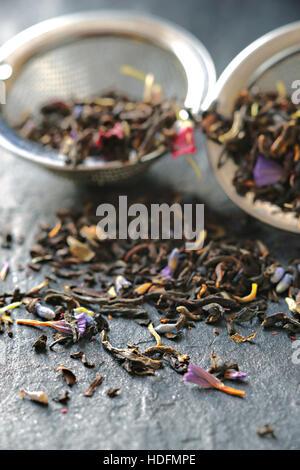Tè con petali di fiori in la succhieruola sulla pietra verticale di sfondo