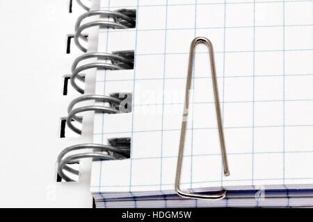 Clip di carta sulle pagine del notebook. Isolato su bianco Foto Stock