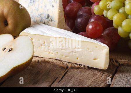 Formaggio stampato, uva e pere vicino sul tavolo. orizzontale in stile rustico Foto Stock