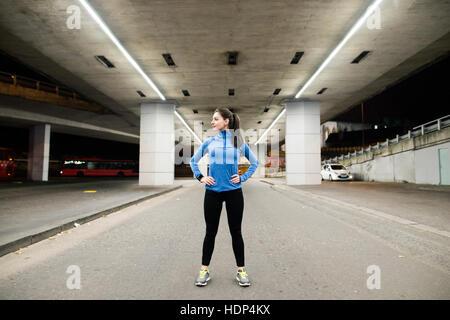 Giovani runner sotto il ponte di sera, in appoggio Foto Stock