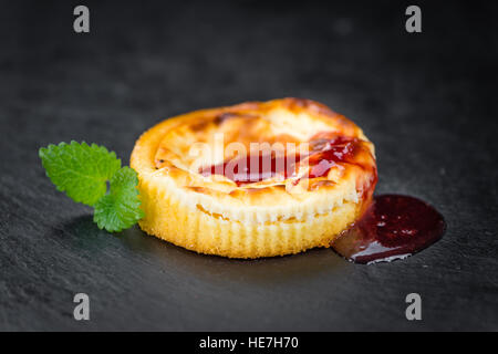 Cheesecake con salsa su un vintage lastra di ardesia (close-up shot; messa a fuoco selettiva) Foto Stock