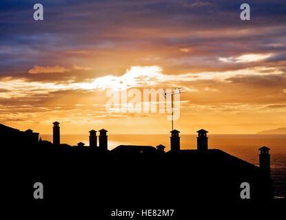 Sunset silhouettes di tetti di case con camini Foto Stock