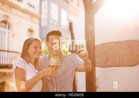 Fortunatamente sorridente giovane prendendo un selfie mentre sollevando i loro bicchieri da birra e sorridente felicemente Foto Stock