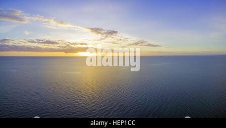 Bella incandescente giallo-viola del tramonto su acque oceaniche con piccole navi a distanza Foto Stock