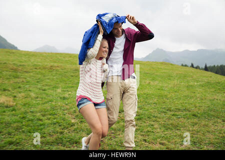 Coppia giovane correndo giù per la collina fino giacca a vento in caso di pioggia, Sattelbergalm, Tirolo, Austria Foto Stock