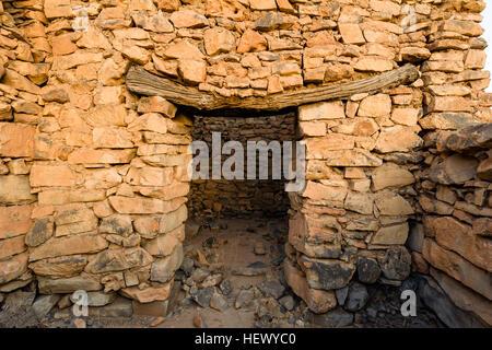 Un antico in pietra fatti a mano della parete edilizia e legname architrave della porta in un deserto abbandonato Foto Stock