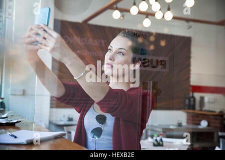 Giovane donna seduta al cafe, tenendo selfie, utilizza lo smartphone Foto Stock