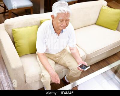 Elevato angolo di visione di un solitario asian senior seduto sul divano con il cellulare in mano. Foto Stock
