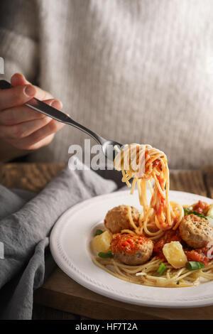 Donna mangiare spaghetti con le polpette di carne e formaggio in verticale Foto Stock
