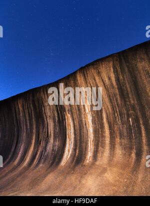 La pendenza svasata di Wave Rock sotto le stelle di notte. Western Australia. Le strisce nere sono causati dalle alghe scolorimento
