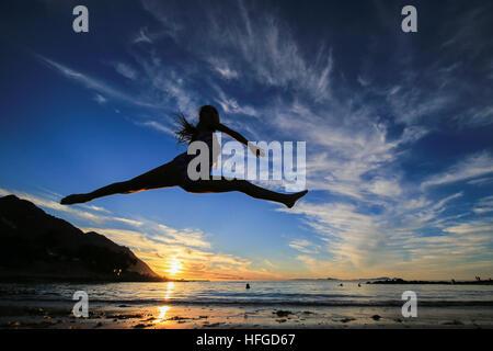 CAPE Town, Sud Africa - Venerdì 30 dicembre 2016, una giovane ragazza fa ballare split salta come il sole tramonta Foto Stock