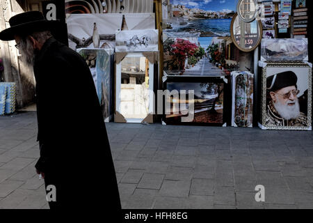 Gerusalemme, Israele. Il 1 di gennaio 2017. Ebraico Ultra-Orthodox uomo cammina davanti ad una vetrina per visualizzare fotografie incorniciate e dipinti. Credito: Nir Alon/Alamy Live News