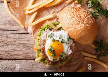 Sandwich con grigliate di carne, un uovo fritto e patatine fritte. vista orizzontale dal di sopra Foto Stock