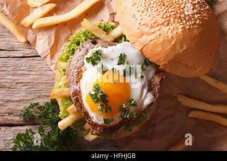 Sandwich con grigliate di carne, un uovo fritto e patatine fritte di close-up. vista orizzontale dal di sopra Foto Stock