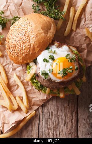 Sandwich con grigliate di carne, un uovo fritto e patatine fritte. verticale vista superiore Foto Stock