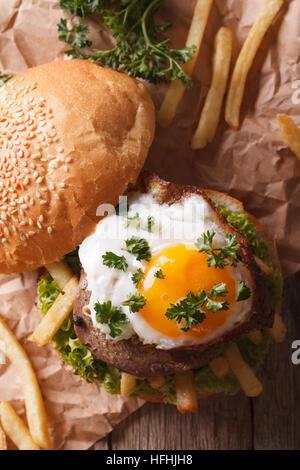 Sandwich con grigliate di carne, un uovo fritto e patatine fritte di close-up. verticale vista superiore Foto Stock