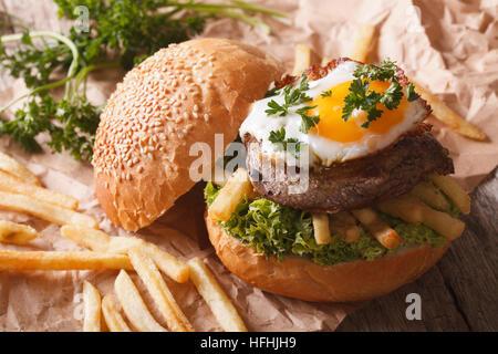 Sandwich rustico con bistecca di manzo, uova fritte e patatine fritte. Posizione orizzontale Foto Stock
