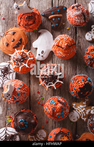 Tortini di Halloween e gingerbread cookies vicino sul tavolo. verticale vista superiore Foto Stock