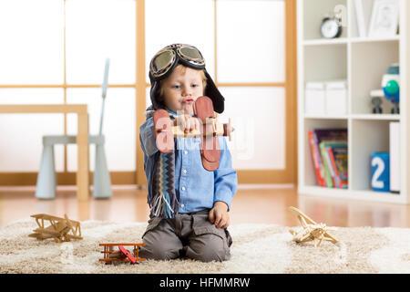 Bambino ragazzo fingendo di essere pilota. Kid giocando con gli aeroplani giocattolo a casa. Viaggi e concetto di Foto Stock