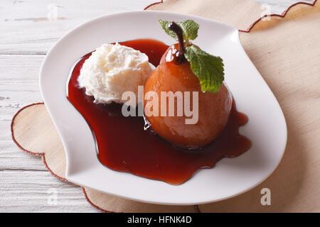 Bellissima cibo: pera affogata di sciroppo e di gelato alla vaniglia close-up su una piastra orizzontale. Foto Stock