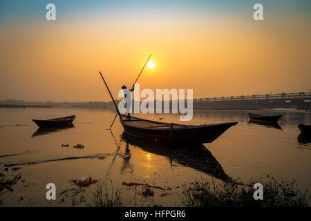 Silhouette barca con rematore al tramonto sul fiume Damodar, Durgapur Barrage, West Bengal, India. Foto Stock
