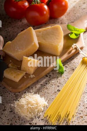 Blocchi di formaggio Parmigiano con pomodori, le foglie di basilico, pasta e formaggio grattugiato Foto Stock