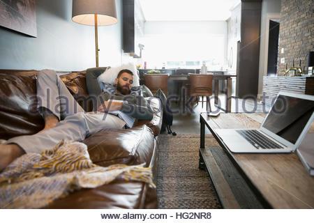 Stanco uomo con libro che dorme sul divano di casa Foto Stock