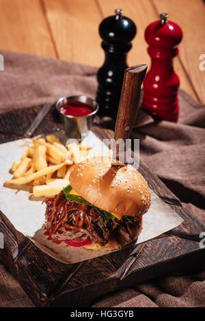 Gustosa burger essendo servito con patate fritte Foto Stock
