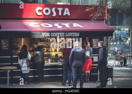 """La gente seduta in una fila al Costa Coffee shop per un caffè freno: """" per gli amanti del caffè' slogan Foto Stock"""