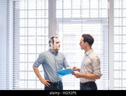 Due colleghi parlare insieme sui documenti di progetto in piedi nel moderno e luminoso interno di office Foto Stock