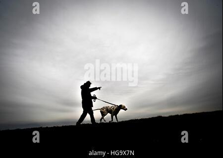 L uomo si prende il suo cane per una passeggiata.