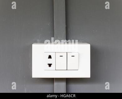 Plastica presa elettrica con interruttore di illuminazione sul muro di casa. Foto Stock