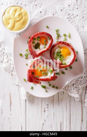 Uova fritte avvolto in pancetta croccante su una piastra con la salsa sul tavolo. verticale vista superiore Foto Stock