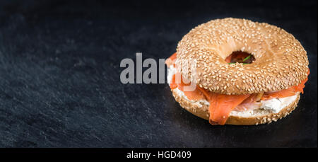 Bagel con salmone su una lastra di ardesia (messa a fuoco selettiva; close-up shot) Foto Stock