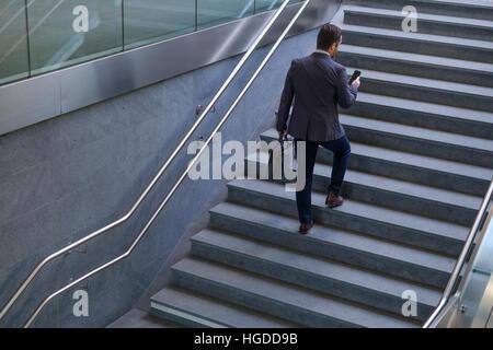 Imprenditore è guardando al suo telefono cellulare mentre sta andando al lavoro Foto Stock
