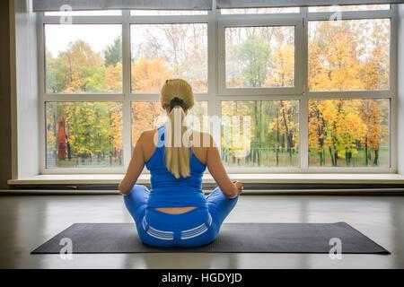 Colpo di idoneità donna seduta sul tappetino di esercizio al fitness club. Foto Stock