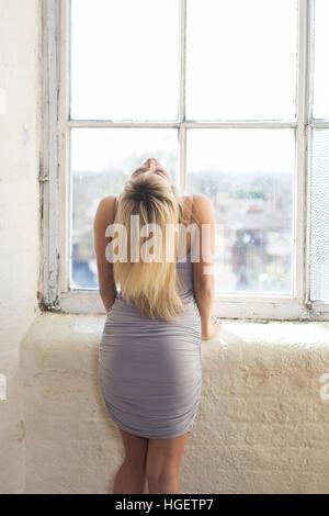 Vista posteriore di una donna bionda in piedi dalla finestra Foto Stock