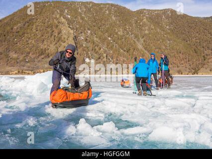 Lago Baikal, Russia - 24 Marzo 2016: gli uomini trascinato la Ice Sledge attraverso una fessura nel ghiaccio del Foto Stock