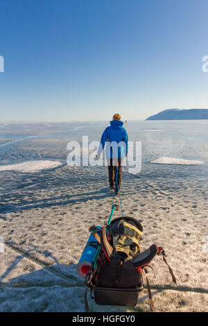 Ragazza con una mazza e trekking pole è sul ghiaccio del lago Baikal. Foto Stock
