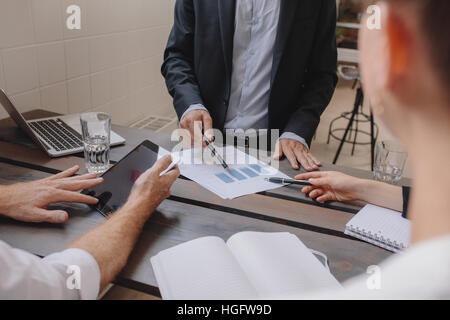 Immagine ravvicinata di team di professionisti riuniti con tavoletta digitale e grafici. La gente di affari per Foto Stock