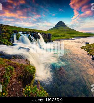 Estate tramonto sulla famosa cascata Kirkjufellsfoss e Kirkjufell mountain.Colorata scena sulla penisola Snaefellsnes,l'Islanda. Foto Stock