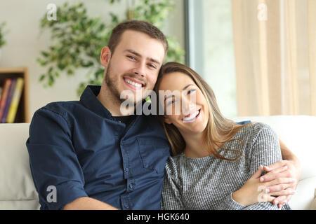 Vista anteriore verticale di una coppia felice in posa e guardando la telecamera seduta su un divano nel salotto Foto Stock