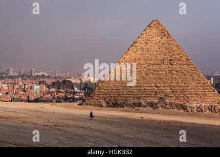 Lone rider su un cammello vicino alla base di una delle piramidi di Giza con la città del Cairo in background. Foto Stock