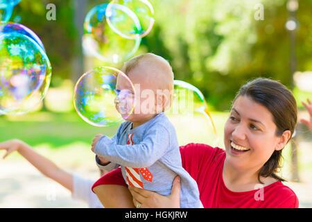 Carino il bambino e sua madre la cattura di bolle di sapone in un giorno di estate Foto Stock