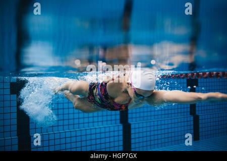 Riprese subacquee di giovani sportive nuoto in piscina. Nuotatore femminile in azione all'interno piscina. Foto Stock