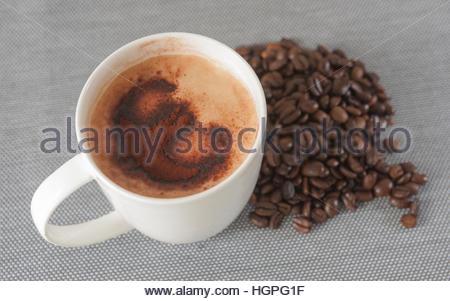 La tazza di caffè latte su un tavolo blu opaco con i chicchi di caffè con simbolo euro in polvere di cacao su schiuma Foto Stock