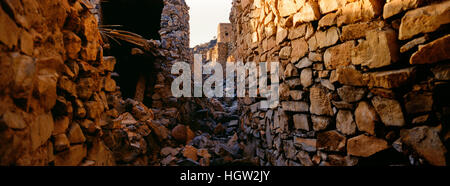 Artigianali antichi edifici in pietra, negozi e case la linea una strada in un villaggio abbandonato. Foto Stock