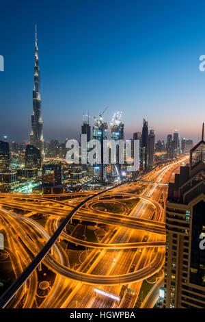 Notte skyline del centro con il Burj Khalifa grattacielo e Sheikh Zayed Road intersezione, Dubai, Emirati Arabi Foto Stock